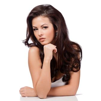 Długie proste włosy. piękna brunetki dziewczyna odizolowywająca na bielu