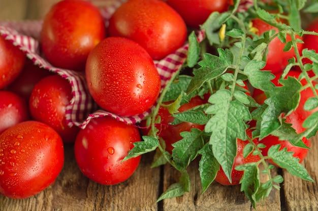 Długie śliwkowe pomidory z kraciastą czerwoną serwetką na drewnianym stole. sterta świeżych pomidorów