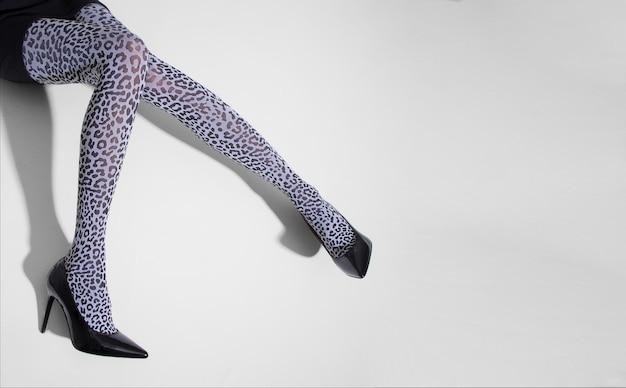 Długie, smukłe nogi młodej kobiety w rajstopach z czarnym tygrysem na żółtym tle. baner w stylu pop-art