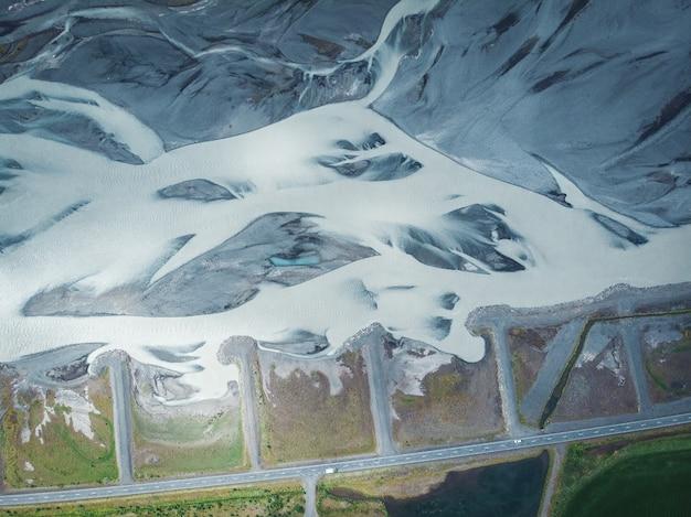 Długie śnieżne wzgórza na islandii z widokiem z góry na drogę i samochody