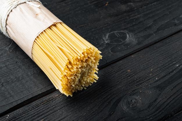 Długie spaghetti. surowy zestaw do spaghetti, na czarnym drewnianym stole
