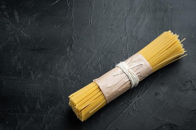 Długie spaghetti. surowy zestaw do spaghetti, na czarnym stole