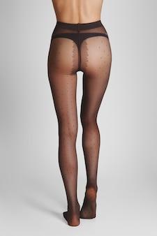 Długie szczupłe kobiece nogi w przezroczystych rajstopach z klasycznym wzorem w kropki