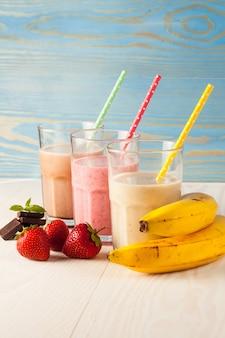 Długie szklanki koktajli mlecznych z czekoladą, truskawką, bananem i lodami na białym tle