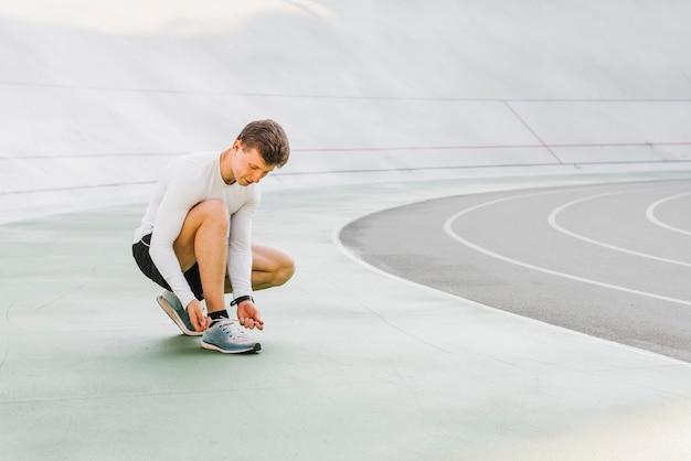 Długie ujęcie biegacza wiążącego jego buty