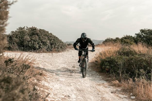 Długie ujęcie człowieka w sprzęt do kolarstwa górskiego