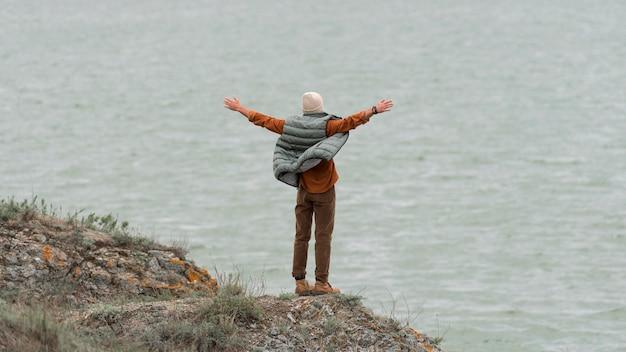 Długie ujęcie człowieka z rękami w powietrzu zwrócone w stronę wody