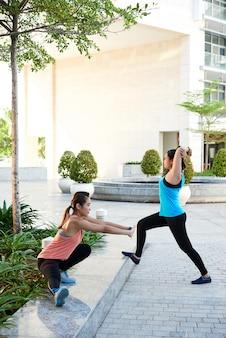 Długie ujęcie dwóch dopasowanych dziewcząt rozciągających się na zewnątrz przed treningiem