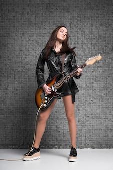 Długie ujęcie gwiazdy rocka grającej na gitarze