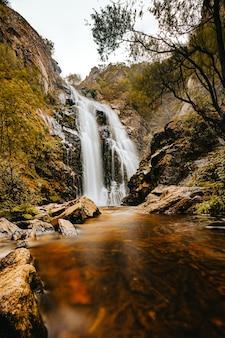 Długie ujęcie jesienią masywnego wodospadu w środku lasu