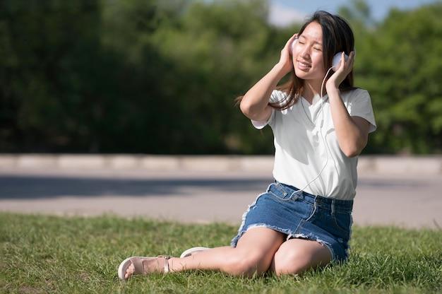 Długie ujęcie kobieta słuchania muzyki przez słuchawki