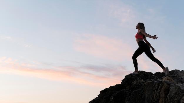 Długie ujęcie kobieta w sportowej stojącej na wybrzeżu z miejsca na kopię