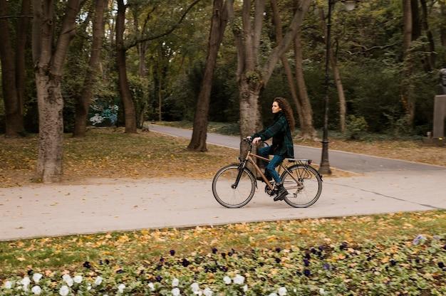 Długie ujęcie kobiety i roweru w parku