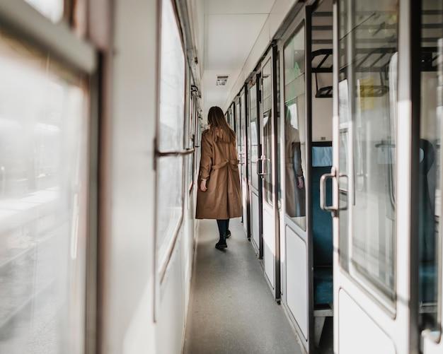 Długie ujęcie kobiety idącej korytarzem pociągu