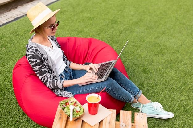 Długie ujęcie kobiety pracującej na jej laptopie