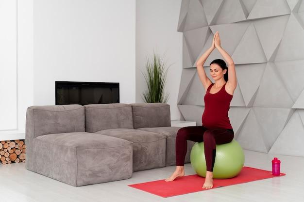 Długie ujęcie kobiety w ciąży za pomocą piłki fitness