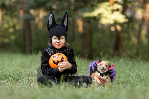 Długie ujęcie małego chłopca w stroju nietoperza i psa