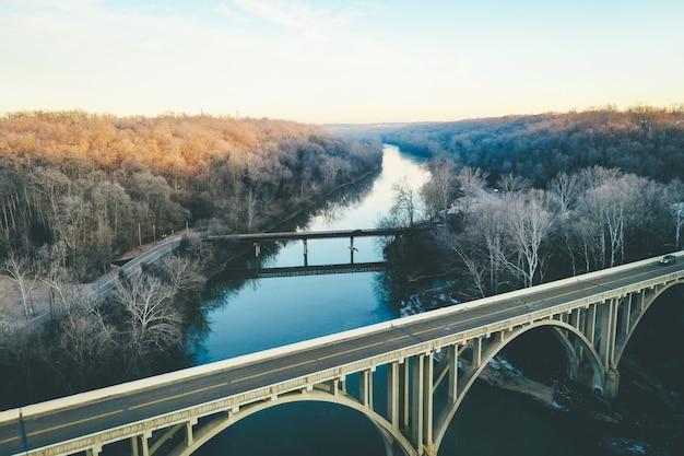 Długie ujęcie malowniczej rzeki z jesiennymi drzewami i łukowym mostem na pierwszym planie