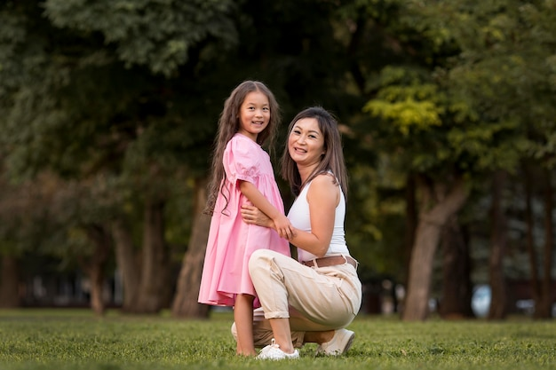 Długie ujęcie matki trzymającej córkę na zewnątrz