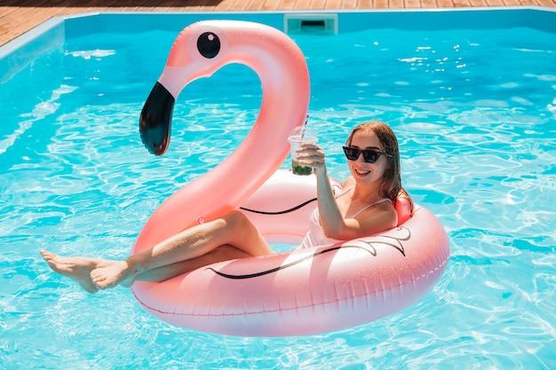 Długie ujęcie młoda kobieta w pierścień pływać