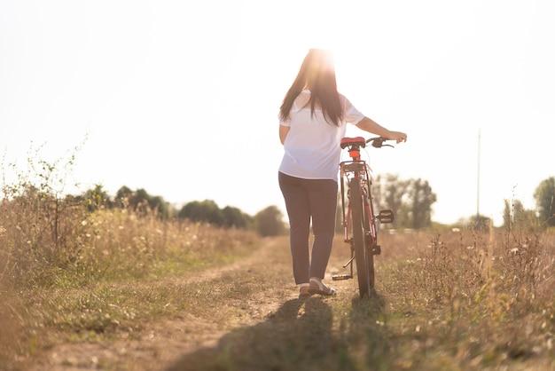 Długie ujęcie młodego człowieka i roweru