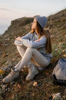 Długie ujęcie młodej kobiety cieszącej się spokojem wokół niej
