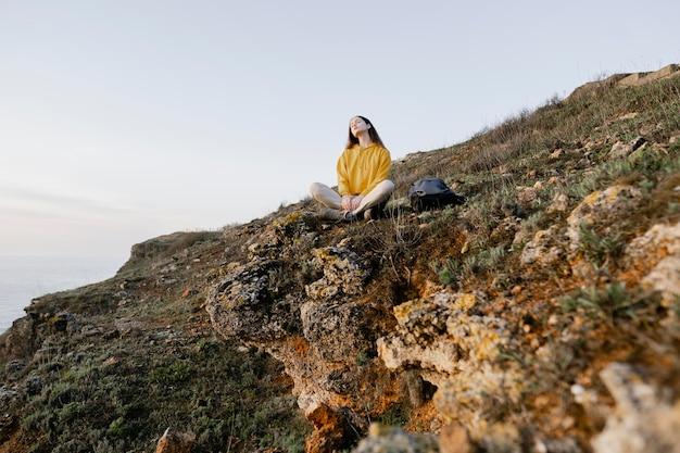 Długie ujęcie młodej kobiety z przyrodą wokół niej