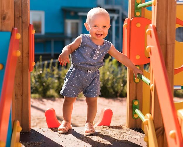 Długie ujęcie piękne dziecko bawiące się na zewnątrz