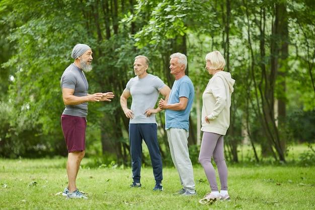 Długie ujęcie przedstawiające profesjonalnego trenera fitness stojącego przed starszymi klientami, wyjaśniającego im coś