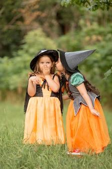Długie ujęcie ślicznych dziewczynek z kostiumami na halloween