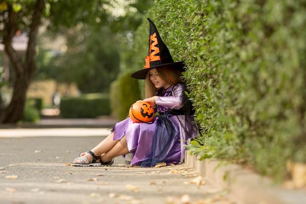 Długie ujęcie słodkie dziewczynki z kostiumem czarownicy