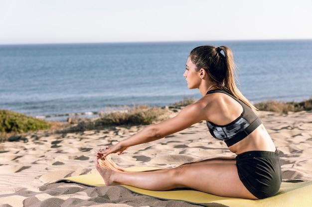 Długie ujęcie sportowa kobieta rozciąga jej nogi na sprawności fizycznej macie