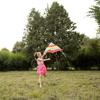 Długie ujęcie szczęśliwej dziewczyny zabawy z latawcem