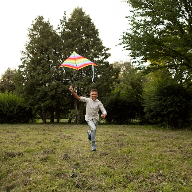 Długie ujęcie szczęśliwy chłopiec zabawy z latawcem