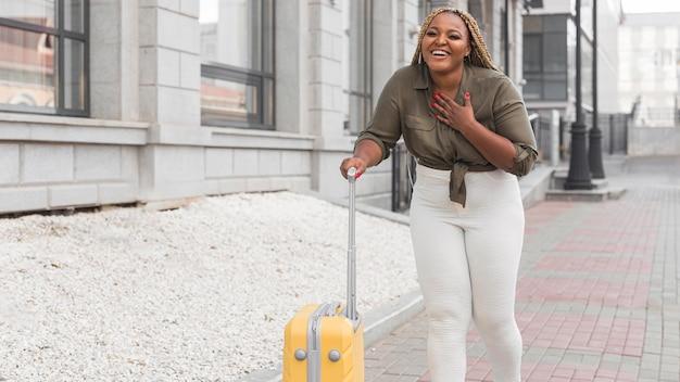 Długie ujęcie uśmiechniętego podróżnika spacerującego po mieście