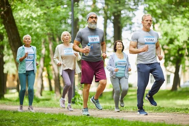 Długie ujęcie zdrowych starszych mężczyzn i kobiet biorących udział w wyścigu maratońskim w parku leśnym w letni dzień