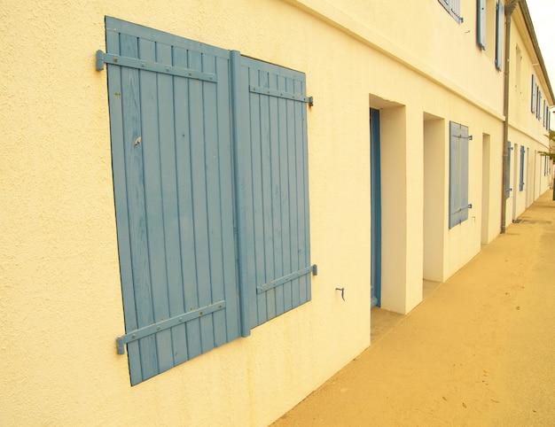 Długie ujęcie żółtej elewacji budynku z niebieskawymi wdowami i drzwiami