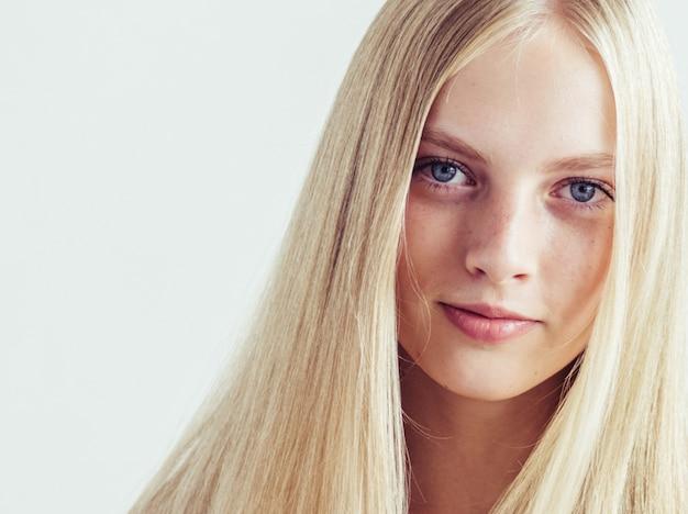 Długie włosy blond młody model. piękna dziewczyna z kędzierzawą idealną fryzurą. strzał studio.