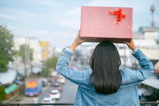 Długie włosy dziewczyna trzymać pudełko na głowie odwrócić. na widok nieba miasta.