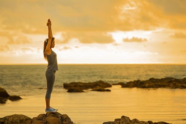 Długie włosy w dobrej formie azjatycka kobieta grająca ćwiczenia jogi na skale o zmierzchu