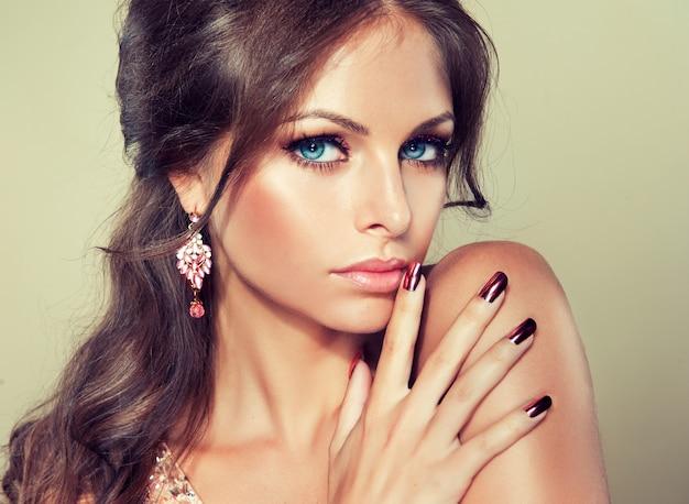 Długie włosy zebrane w elegancką, swobodnie układającą się fryzurę. niebieskooka młoda kobieta z jasny makijaż wieczorowy na twarzy i złocony manicure na palcach. sztuka fryzjerska, makijaż i manicure.