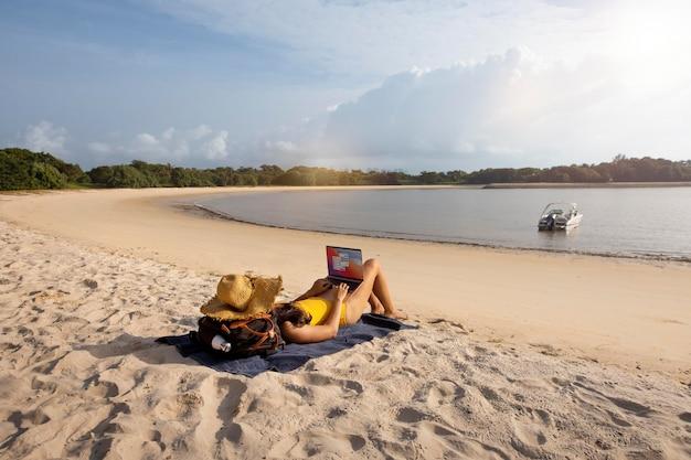 Długie zdjęcie kobiety pracującej na plaży z laptopem