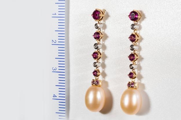Długie złote kolczyki z brylantami, rubinami i perłami na białym tle obok linijki