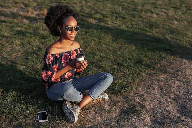 Długiego przedstawienia piękna afrykańska kobieta patrzeje daleko od