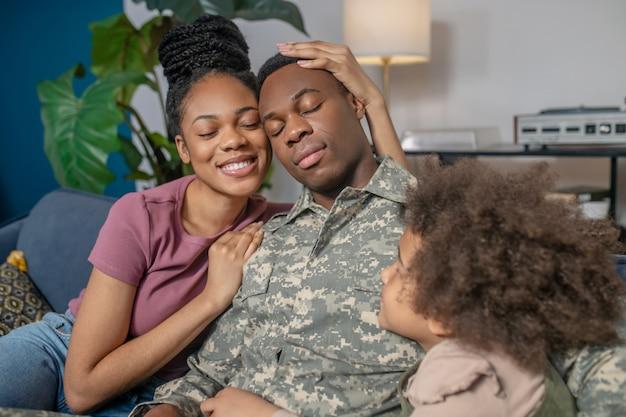 Długo oczekiwane spotkanie. afroamerykanka młoda kobieta przytulająca wojskowego męża wracającego do domu siedzącego z zamkniętymi oczami i małą dziewczynką