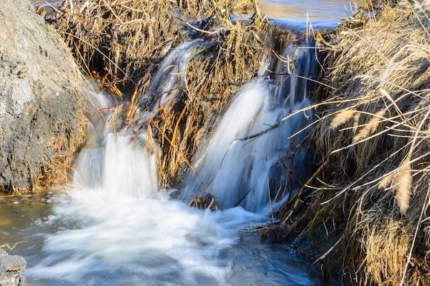 Długo wyczekiwane wiosenne strumienie przepływają w słoneczny dzień nad wąwozami i wzgórzami. wodospady i wodospady strumieni wśród suchej trawy. piękny wiosenny krajobraz.