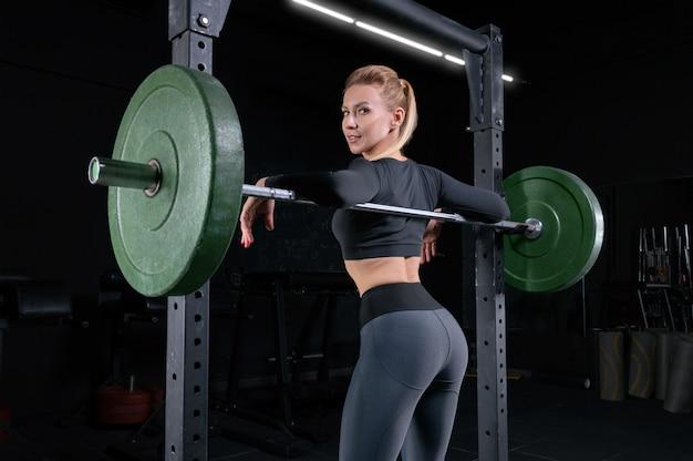 Długonoga dziewczyna pozuje na siłowni. oparła się o sztangę. pojęcie sportu, kulturystyki, fitness, aerobiku. zdrowy tryb życia. różne środki przekazu