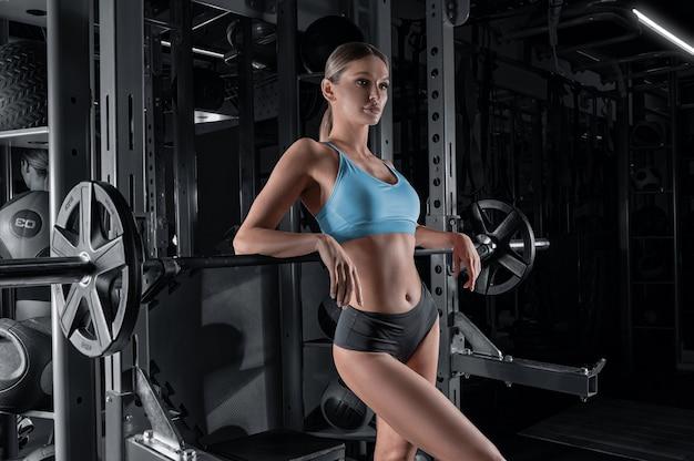 Długonoga dziewczyna pozuje na siłowni. oparła się o sztangę.