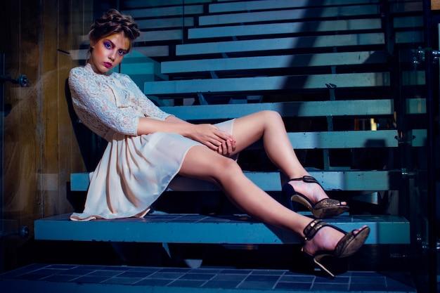 Długonoga kobieta w białej sukni siedzi na schodach i pozuje