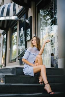 Długonoga piękna dziewczyna w niebieskiej sukience siedzi na czarnych marmurowych schodach, jest uśmiechnięta i bardzo szczęśliwa